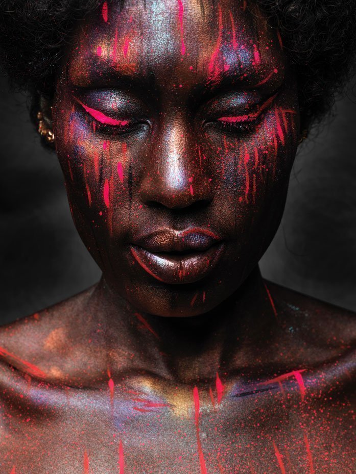 Black woman with her eyes closed and paint dripping down her face