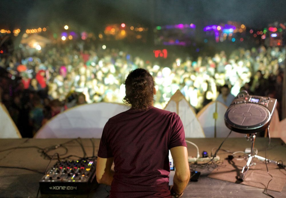 Musician David Starfire on a music festival stage looking at crowd